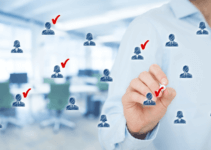 Man Selecting Candidate Icons from Group Floating In Front of Him with Red Check Marks