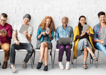 Young-people-on-devices-smiling-sitting-next-to-each-other