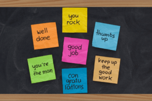 Chalkboard with Multicolored Sticky Notes that Have Encouraging Phrases Written on Them
