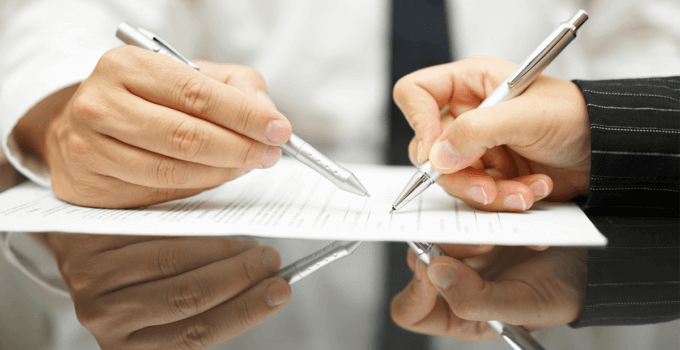 Man Hand Pointing Out Where to Sign as Woman Hand Signs Document