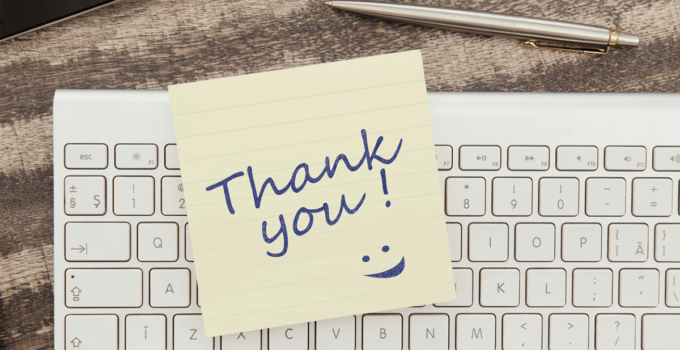 Sticky Note on Top of Keyboard with Thank You and a Smiley Face Written in Blue Pen