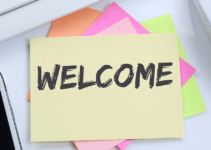 Welcome Written on Top Sticky in Pile in Between Phone and Mouse on Table