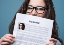Young Woman with Glasses Holding Resume Up Partially Covering Face on Blue Background