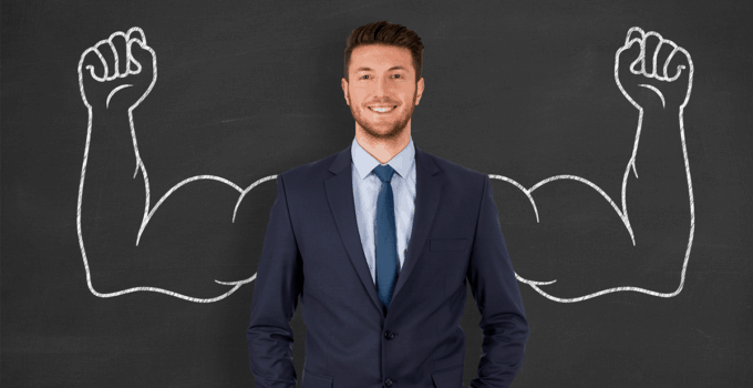 Businessman Standing in Front of Chalkboard with Muscular Chalk Arms Drawn Behind Him