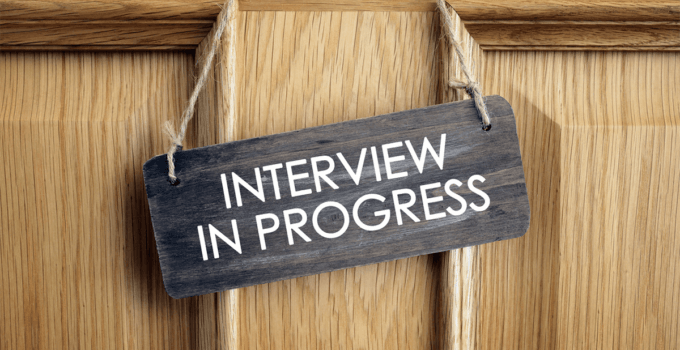 Dark Interview In Progress Sign Hanging from Light Wood Door - Interview Q&A Don'ts