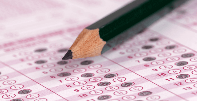 Pink Scantron in Deep Focus with Answers Filled in and Black Pencil in Foreground