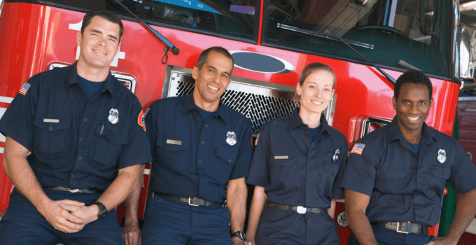 Happy Firefighters Leaning Against Front of Fire Truck