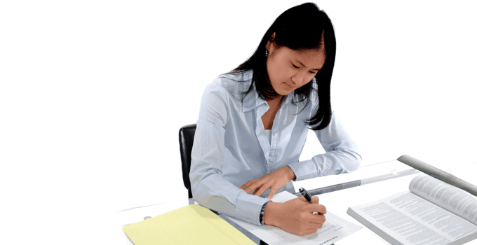 Young Woman Taking Paper Assessment on Table with Books (1)