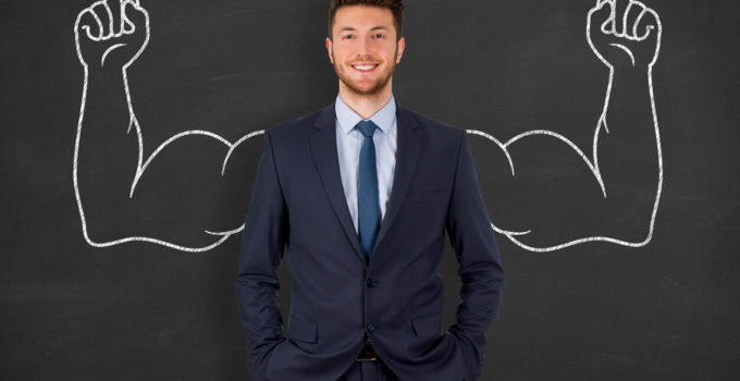 Businessman in Front of Chalkboard with Muscular Arms Drawn Behind