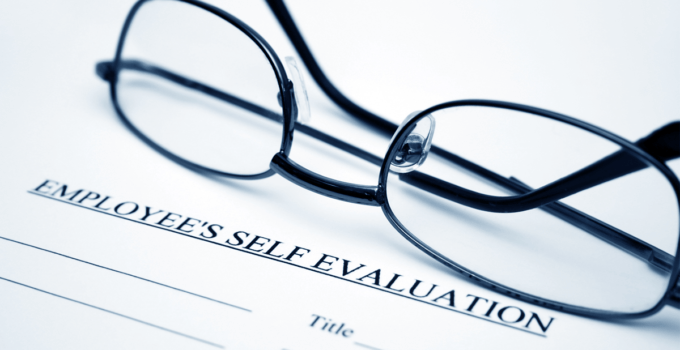 Glasses Set on Top of Employee Self-Evaluation Papers