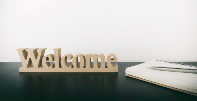 Welcome Decoration Sitting on Black Desk with Blank Notebook Sitting Beside Welcoming New Employee