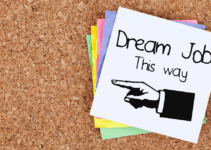 Dream Job This Way Written with Drawn Hand Pointing Left on Top Sticky Note in Pile on Cork Background