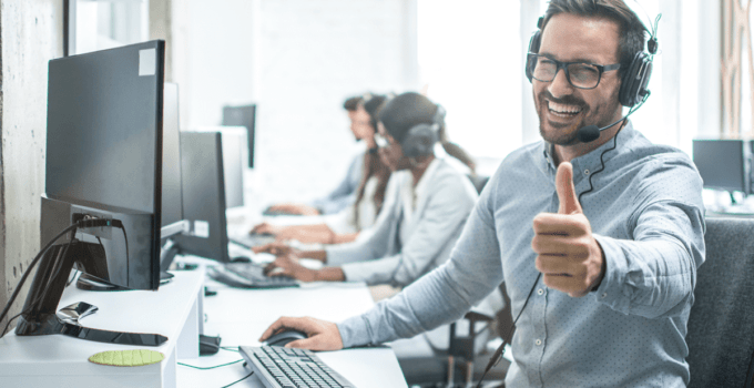 Man with Glasses Wearing Headset in Front of Computer Smiling and Giving Thumbs Up