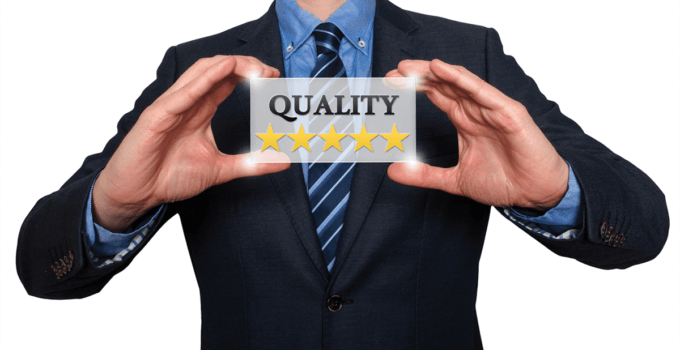 Businessman Holding Up Translucent Sign that Says Quality with Five Stars Below