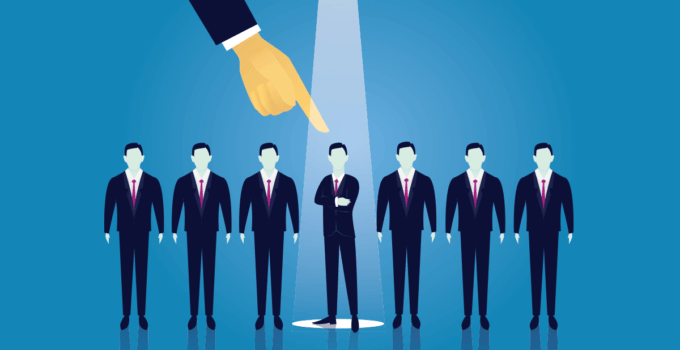 Businessman's Hand Pointing Down to Center Man in Line of Suited Men with Spotlight on Him