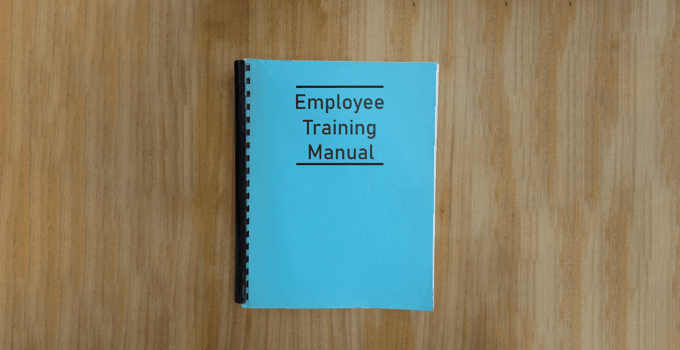Blue Bound Book with Employee Training Manual on Cover Sitting on Light Wood Desk