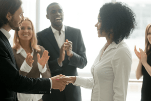 Group of Businesspeople Clapping in Congratulations for Young Woman Shaking Boss's Hand