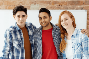 Three Young People Arm-In-Arm in Office Workroom in Front of Whiteboard