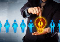 Line of Blue Businesspeople Icons in Front of Man in Suit Pointing to One Orange Man Icon in Lightbulb