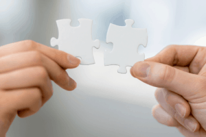 Man and Woman's Hands Holding White Jigsaw Puzzle Pieces Together