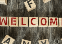Welcome Written on Wooden Blocks in Red on Wooded Table with Other Block Scattered Around
