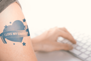 How 4 Major Companies are Retaining Employees - Person Typing at Keyboard with Closeup of I Love My Company Tattoo on Arm